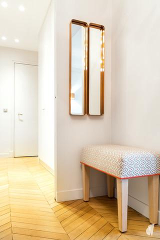 Aménagement et décoration d'un double salon et entrée dans un appartement Haussmannien revisité à l'ambiance design à Paris, par le Studio Coralie Vasseur. Coralie Vasseur est votre architecte d'intérieur et décoratrice UFDI à Annecy, Genève et en Haute Savoie : zoom sur le banc sur mesure et les miroirs cuivrés de l'entrée