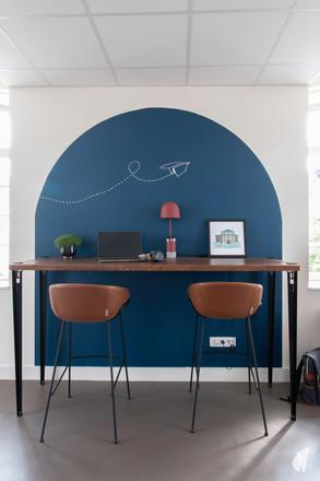 Aménagement et décoration des bureaux d'une startup à Senlis, par l'agence Coralie Vasseur. Coralie Vasseur est votre architecte d'intérieur et décoratrice UFDI à Annecy, Genève et en Haute Savoie : color zoning bleu avec bureau assis debout