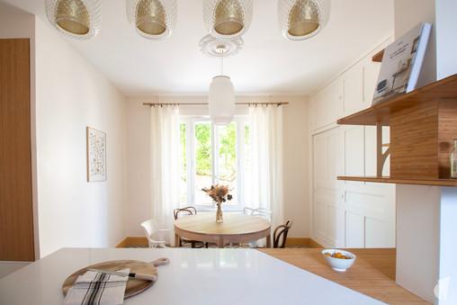 Création d'une cuisine au design sur-mesure à Annecy, par le Studio Coralie Vasseur. Coralie Vasseur est votre architecte d'intérieur et décoratrice UFDI à Annecy, Megève et en Haute Savoie : séparation en biseau du plan de travail entre bambou et quartz, avec vue sur la salle à manger