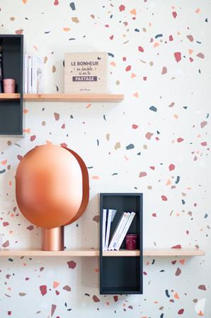 Rénovation et décoration d'une maison bourgeoise à Genève, par le Studio Coralie Vasseur. Coralie Vasseur est votre architecte d'intérieur et décoratrice UFDI à Annecy, Genève et en Haute Savoie : Zoom sur la lampe cuivrée devant le mur terrazzo