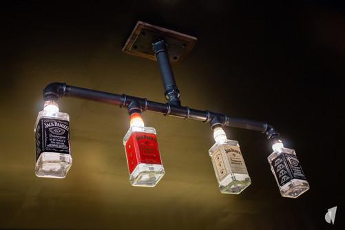 Aménagement et décoration d'un bar restaurant industriel jungle à Compiègne, par l'agence Coralie Vasseur. Coralie Vasseur est votre architecte d'intérieur et décoratrice UFDI à Annecy, Genève et en Haute Savoie : suspension luminaire en bouteilles d'alcool recyclées