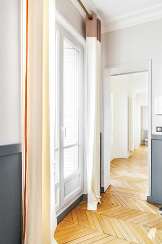 Aménagement et décoration d'un double salon et entrée dans un appartement Haussmannien revisité à l'ambiance design à Paris, par le Studio Coralie Vasseur. Coralie Vasseur est votre architecte d'intérieur et décoratrice UFDI à Annecy, Genève et en Haute Savoie : focus sur les détails des rideaux sur mesure avec leur galon et leur tête à oeillets