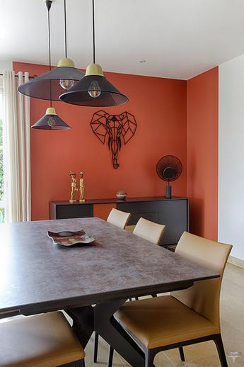 Décoration d'une pièce de vie contemporaine à l'ambiance voyage par Carnets Libellule. Coralie Vasseur est votre Décoratrice d'intérieur UFDI à Compiegne : espace repas salle à manger avec mur terracotta, implantation de couleur originale et asymétrique en retour d'angle