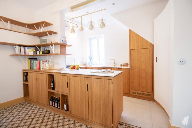 Création d'une cuisine au design sur-mesure à Annecy, par le Studio Coralie Vasseur. Coralie Vasseur est votre architecte d'intérieur et décoratrice UFDI à Annecy, Megève et en Haute Savoie : vue d'ensemble de la cuisine en bambou avec sa porte courbe en acier