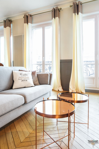 Décoration d'un double salon moderne dans un appartement Haussmannien à Paris 17 par Carnets Libellule. Coralie Vasseur est votre Décoratrice d'intérieur UFDI à Compiegne : canapé gris moderne et tables basses rondes cuivrées pour coin TV
