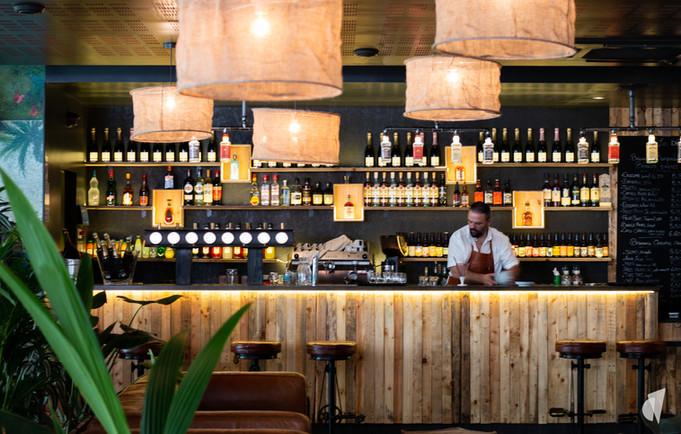 Aménagement et décoration d'un bar restaurant industriel jungle à Compiègne, par l'agence Coralie Vasseur. Coralie Vasseur est votre architecte d'intérieur et décoratrice UFDI à Annecy, Genève et en Haute Savoie : bar et ses suspensions en toile de jute, ambiance voyages