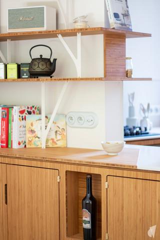Création d'une cuisine au design sur-mesure à Annecy, par le Studio Coralie Vasseur. Coralie Vasseur est votre architecte d'intérieur et décoratrice UFDI à Annecy, Megève et en Haute Savoie : détail sur la cuisine en bambou et acier, avec étagères aux formes organiques et quincaillerie en laiton