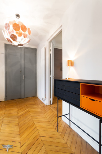 Décoration d'un double salon moderne dans un appartement Haussmannien à Paris 17 par Carnets Libellule. Coralie Vasseur est votre Décoratrice d'intérieur UFDI à Compiegne : entrée lumineuse avec parquet en point de Hongrie et suspension cuivrée