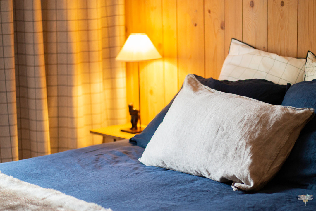 Décoration d'un chalet de montagne à Val d'Isère, par Carnets Libellule. Coralie Vasseur est votre architecte d'intérieur UFDI en Savoie et sur toute la France : zoom sur le linge de lit en lin lavé bleu nuit et kaki, rideaux à carreaux sur-mesure