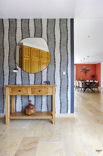 Décoration d'une pièce de vie contemporaine à l'ambiance voyage par Carnets Libellule. Coralie Vasseur est votre Décoratrice d'intérieur UFDI à Compiegne : papier peint à rayures zébrées d'éditeur Elitis sur le mur de l'entrée et miroir aux bords fins