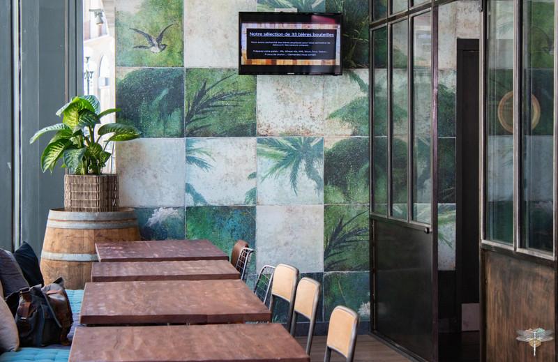 Agencement et décoration du restaurant industriel voyage EAP's CAFE par Carnets Libellule. Coralie Vasseur est votre Décoratrice d'intérieur UFDI à Compiegne : espace privatisable derrière la verrière, papier peint jungle damier