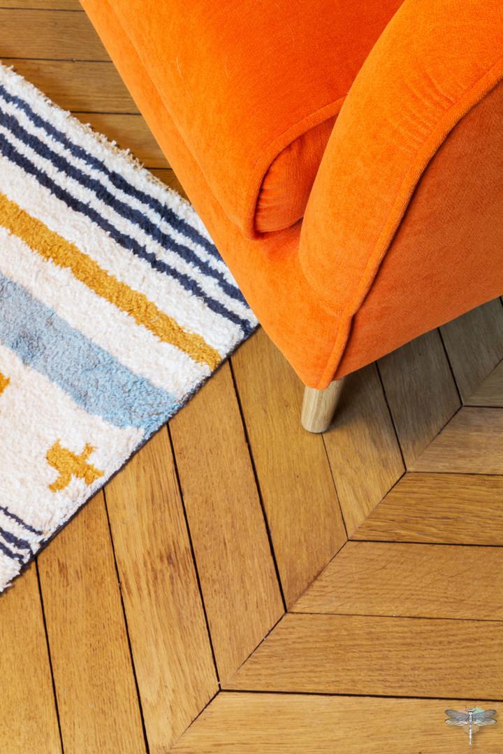 Décoration d'un double salon moderne dans un appartement Haussmannien à Paris 17 par Carnets Libellule. Coralie Vasseur est votre Décoratrice d'intérieur UFDI à Compiegne : parquet chevrons, tapis éditeur et fauteuil Sits