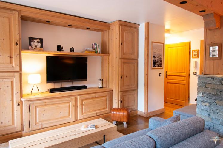 Décoration d'un chalet de montagne à Val d'Isère, par Carnets Libellule. Coralie Vasseur est votre architecte d'intérieur UFDI en Savoie et sur toute la France : agencement en bois massif dans le coin salon TV