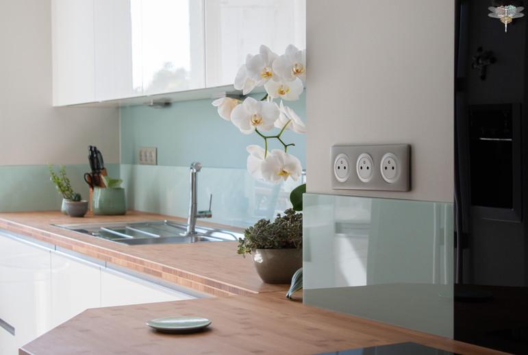 Agencement et décoration d'une cuisine moderne à Senlis dans l'Oise par Carnets Libellule. Coralie Vasseur est votre Décoratrice d'intérieur UFDI à Compiegne : plan de travail en bois et crédence vert d'eau, meubles hauts suspendus laque blanche