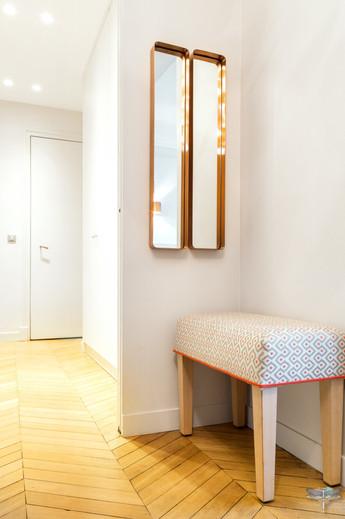 Décoration d'un double salon moderne dans un appartement Haussmannien à Paris 17 par Carnets Libellule. Coralie Vasseur est votre Décoratrice d'intérieur UFDI à Compiegne : dressing d'entrée cloisonné derrière miroirs cuivrés