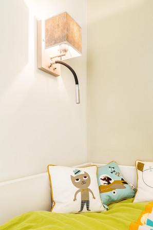 Aménagement et décoration d'une chambre d'enfant garçon à Paris, par le Studio Coralie Vasseur. Coralie Vasseur est votre architecte d'intérieur et décoratrice UFDI à Annecy, Genève et en Haute Savoie : applique liseuse pour le lit et coussins déco kids