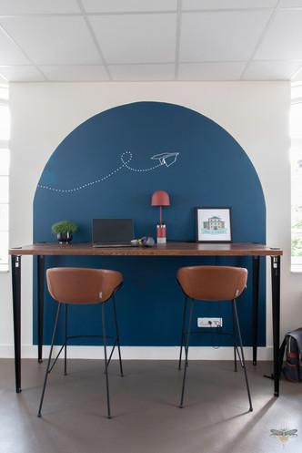 Aménagement et décoration d'un espace de bureaux professionnels à Senlis, pour DecoWorkers, par Carnets Libellule. Coralie Vasseur est votre architecte d'intérieur UFDI à Compiegne : espace de travail assis-debout avec color zoning bleu en forme d'arche et plan de travail assis-debout