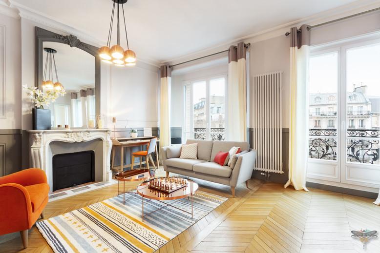 Décoration d'un double salon moderne dans un appartement Haussmannien à Paris 17 par Carnets Libellule. Coralie Vasseur est votre Décoratrice d'intérieur UFDI à Compiegne : vue d'ensemble du salon de réception, parquet en point de Hongrie