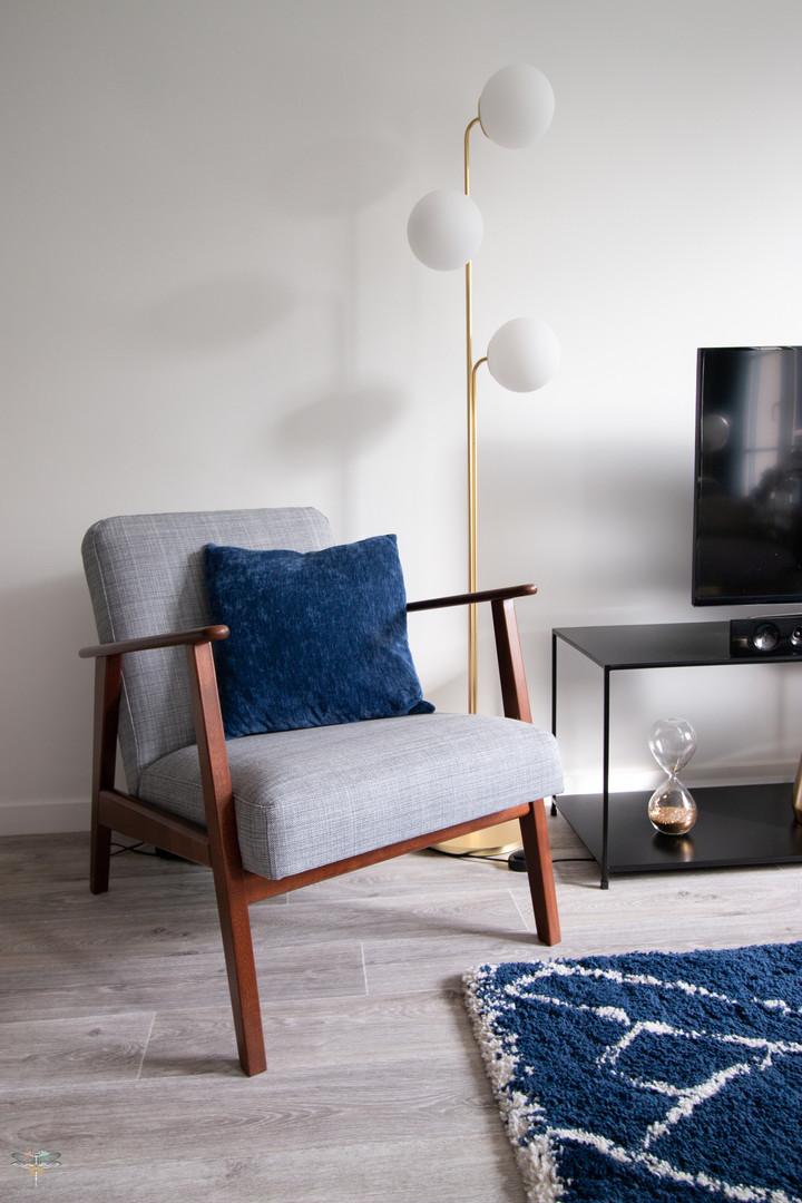 Décoration d'une pièce de vie chic et poétique à Compiègne par Carnets Libellule. Coralie Vasseur est votre Décoratrice d'intérieur UFDI dans l'Oise : zoom sur le fauteuil vintage en bois et tissu, et le lampadaire laiton