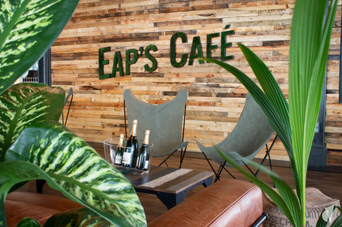 Aménagement et décoration d'un bar restaurant industriel jungle à Compiègne, par l'agence Coralie Vasseur. Coralie Vasseur est votre architecte d'intérieur et décoratrice UFDI à Annecy, Genève et en Haute Savoie : logo végétal sur mur en bois recyclé