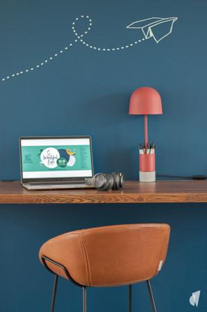 Aménagement et décoration des bureaux d'une startup à Senlis, par l'agence Coralie Vasseur. Coralie Vasseur est votre architecte d'intérieur et décoratrice UFDI à Annecy, Genève et en Haute Savoie : plan de travail en bois, mur bleu et sticker poetic wall