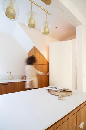 Création d'une cuisine au design sur-mesure à Annecy, par le Studio Coralie Vasseur. Coralie Vasseur est votre architecte d'intérieur et décoratrice UFDI à Annecy, Megève et en Haute Savoie : porte courbe en acier dans cuisine sur-mesure en bambou et quartz, ambiance japandi