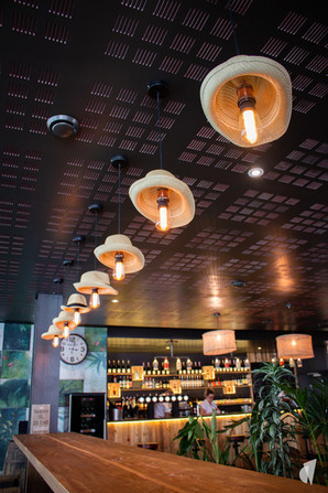 Aménagement et décoration d'un bar restaurant industriel jungle à Compiègne, par l'agence Coralie Vasseur. Coralie Vasseur est votre architecte d'intérieur et décoratrice UFDI à Annecy, Genève et en Haute Savoie : suspensions diy upcycling avec chapeaux de paille