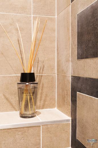 Rénovation et décoration d'une salle d'eau aux couleurs naturelles à Paris par Carnets Libellule. Coralie Vasseur est votre Décoratrice d'intérieur UFDI à Compiegne : détail faïence aux teintes chaudes et modernes