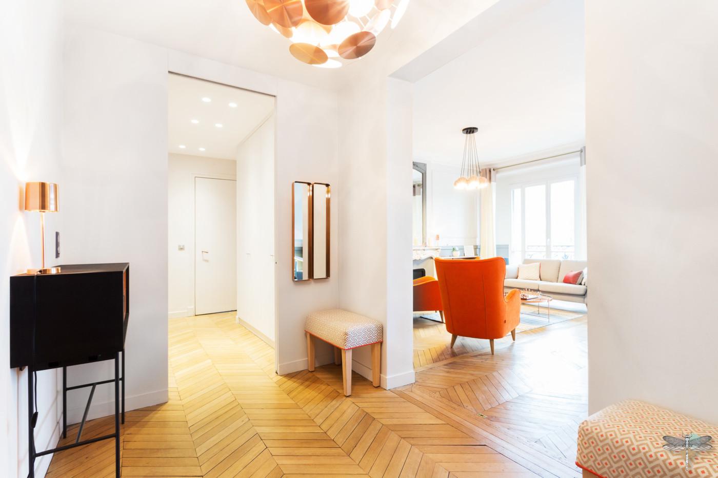 Décoration d'un double salon moderne dans un appartement Haussmannien à Paris 17 par Carnets Libellule. Coralie Vasseur est votre Décoratrice d'intérieur UFDI à Compiegne : grande entrée avec console et vue sur le salon et son fauteuil orange