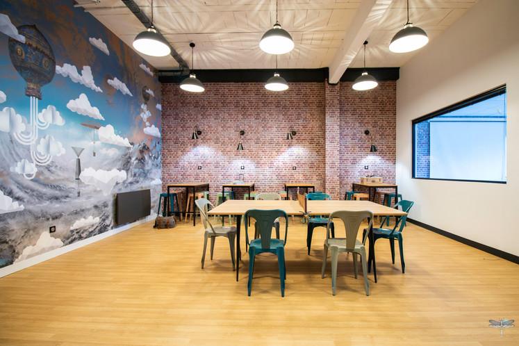 Aménagement et décoration d'un espace de pause à l'école du numérique l'Ascenseur 301, à Compiègne, par Carnets Libellule. Coralie Vasseur est votre architecte d'intérieur UFDI à Compiegne : vue d'ensemble sur l'espace haut de plafond avec son papier peint panoramique, le mur de briques et le mobilier