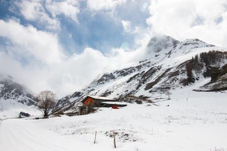 Chalet rouge dans paysage de montagne sous la neige
