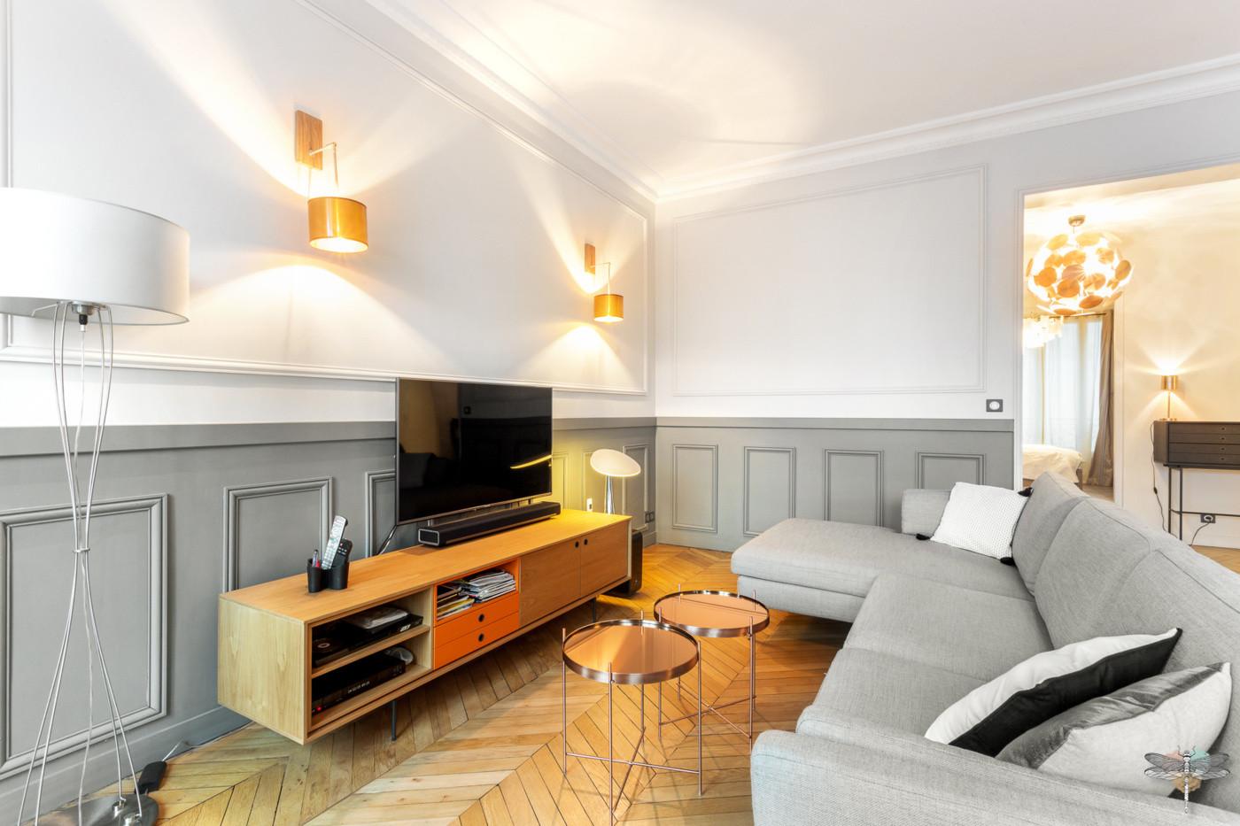 Décoration d'un double salon moderne dans un appartement Haussmannien à Paris 17 par Carnets Libellule. Coralie Vasseur est votre Décoratrice d'intérieur UFDI à Compiegne : espace télévision avec grand canapé d'angle et meuble tv bas sur pieds