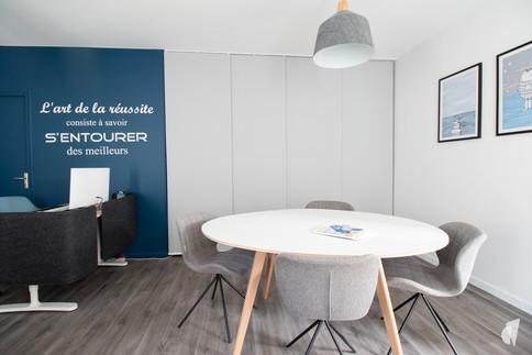 Rénovation et décoration d'une agence de recrutement et coaching à Chantilly, par l'agence Coralie Vasseur. Coralie Vasseur est votre architecte d'intérieur et décoratrice UFDI à Annecy, Genève et en Haute Savoie : espace de réunion convivial avec citation au mur et bureau