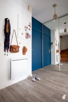 Aménagement et décoration d'une d'une pièce de vie à l'ambiance chic et poétique à Annecy, par l'agence Coralie Vasseur. Coralie Vasseur est votre architecte d'intérieur et décoratrice UFDI à Annecy, Genève et en Haute Savoie : color zoning dans l'entrée avec la porte peinte en bleu qui se reflète dans le miroir comme un agrandissement de la pièce