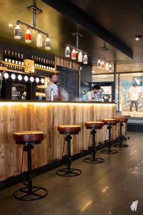 Aménagement et décoration d'un bar restaurant industriel jungle à Compiègne, par l'agence Coralie Vasseur. Coralie Vasseur est votre architecte d'intérieur et décoratrice UFDI à Annecy, Genève et en Haute Savoie : bar en bois et métal rétroéclairé