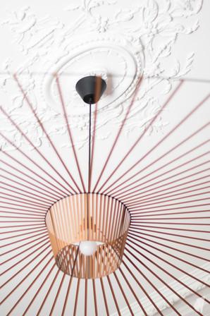 Rénovation et décoration d'une maison bourgeoise à Genève, par le Studio Coralie Vasseur. Coralie Vasseur est votre architecte d'intérieur et décoratrice UFDI à Annecy, Genève et en Haute Savoie : détail de la suspension Vertigo et de la moulure au plafond