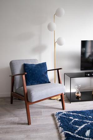 Aménagement et décoration d'une d'une pièce de vie à l'ambiance chic et poétique à Annecy, par l'agence Coralie Vasseur. Coralie Vasseur est votre architecte d'intérieur et décoratrice UFDI à Annecy, Genève et en Haute Savoie : fauteuil vintage en tissu et bois dans le salon, lampadaire en laiton