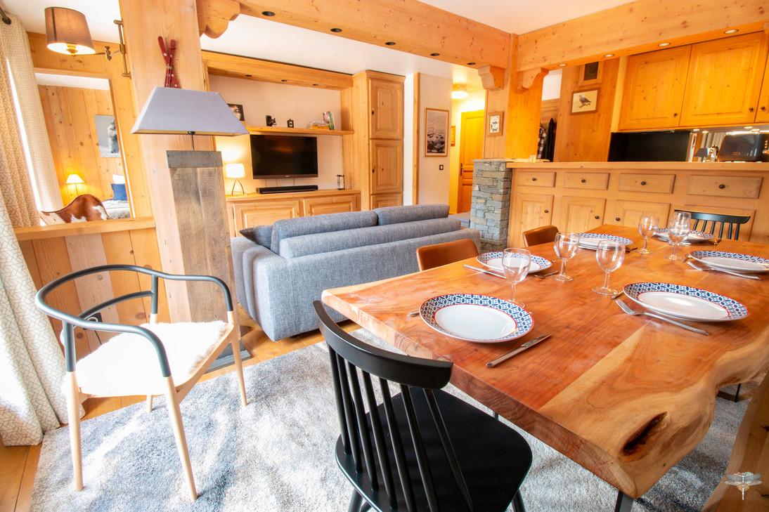 Décoration d'un chalet de montagne à Val d'Isère, par Carnets Libellule. Coralie Vasseur est votre architecte d'intérieur UFDI en Savoie et sur toute la France : Vue d'ensemble depuis la salle à manger sur la pièce de vie. Table à dîner en bois massif