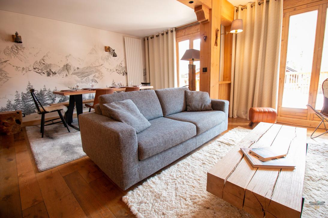 Décoration d'un chalet de montagne à Val d'Isère, par Carnets Libellule. Coralie Vasseur est votre architecte d'intérieur UFDI en Savoie et sur toute la France : vue d'ensemble sur le salon et le canapé en tissu convertible, table basse en bois massif, papier peint panoramique
