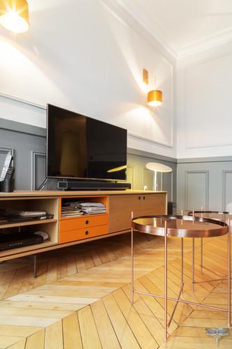 Décoration d'un double salon moderne dans un appartement Haussmannien à Paris 17 par Carnets Libellule. Coralie Vasseur est votre Décoratrice d'intérieur UFDI à Compiegne : meuble TV sur mesure en bois et couleur orange