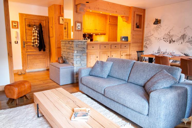 Décoration d'un chalet de montagne à Val d'Isère, par Carnets Libellule. Coralie Vasseur est votre architecte d'intérieur UFDI en Savoie et sur toute la France : vue d'ensemble sur le salon et l'entrée, bar de la cuisine en bois massif