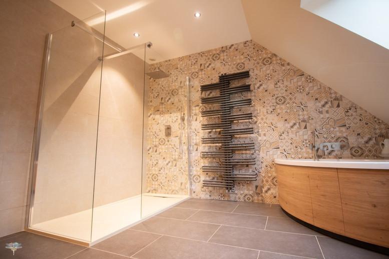 Agencement et décoration d'une salle de bains par Carnets Libellule. Coralie Vasseur est votre Décoratrice d'intérieur UFDI à Compiegne : vue d'ensemble d'une grande salle de bains sur-mesure avec douche avec receveur extra plat, baignoire et sèche-serviette design moderne gris