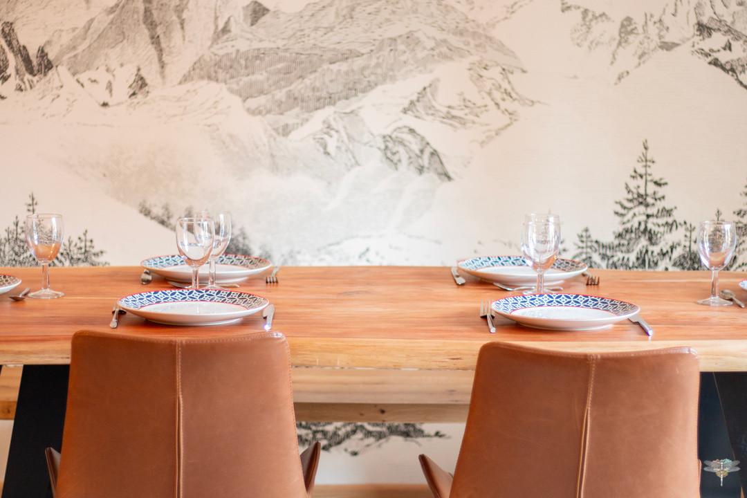 Décoration d'un chalet de montagne à Val d'Isère, par Carnets Libellule. Coralie Vasseur est votre architecte d'intérieur UFDI en Savoie et sur toute la France : zoom sur l'espace repas avec les chaises en cuir, la table en bois massif et le papier peint panoramique montagne noir et blanc