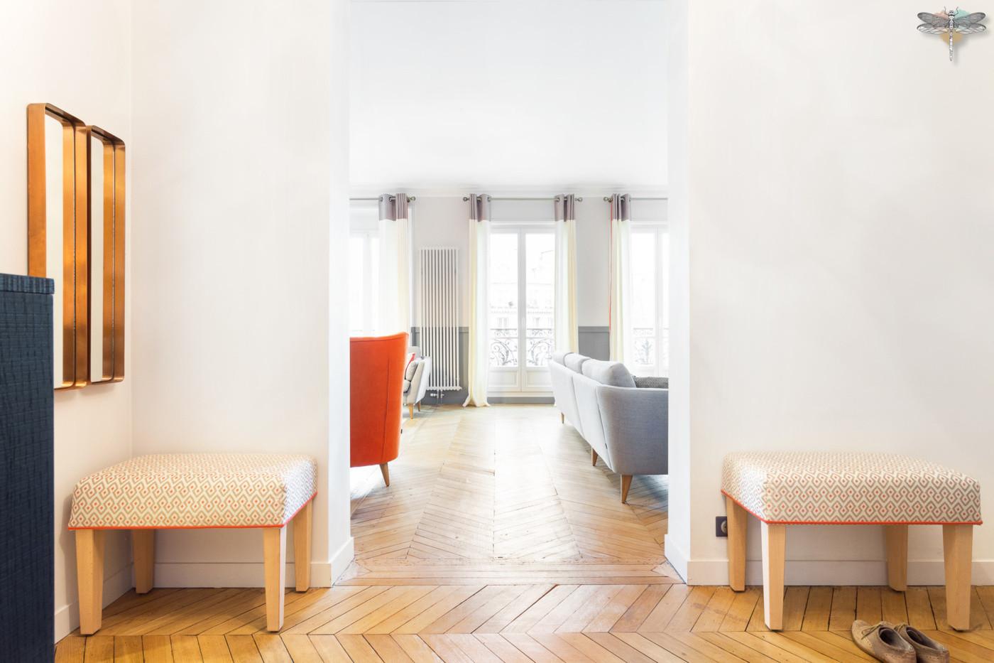Décoration d'un double salon moderne dans un appartement Haussmannien à Paris 17 par Carnets Libellule. Coralie Vasseur est votre Décoratrice d'intérieur UFDI à Compiegne : entrée ouverte sur salon, bancs et mi