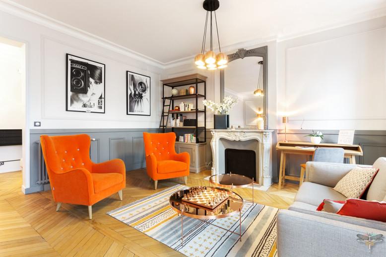 Décoration d'un double salon moderne dans un appartement Haussmannien à Paris 17 par Carnets Libellule. Coralie Vasseur est votre Décoratrice d'intérieur UFDI à Compiegne : vue d'ensemble du salon de réception et ses deux fauteuils orange, sous-bassement gris et cheminée ancienne