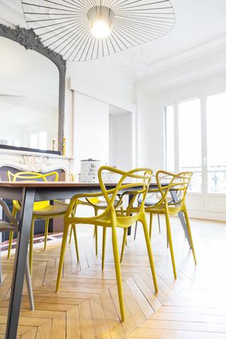 Aménagement et décoration d'une cuisine dans un appartement Haussmannien revisité à l'ambiance design à Paris, par le Studio Coralie Vasseur. Coralie Vasseur est votre architecte d'intérieur et décoratrice UFDI à Annecy, Genève et en Haute Savoie : focus sur les chaises Masters Kartell jaune moutarde dans la salle à manger