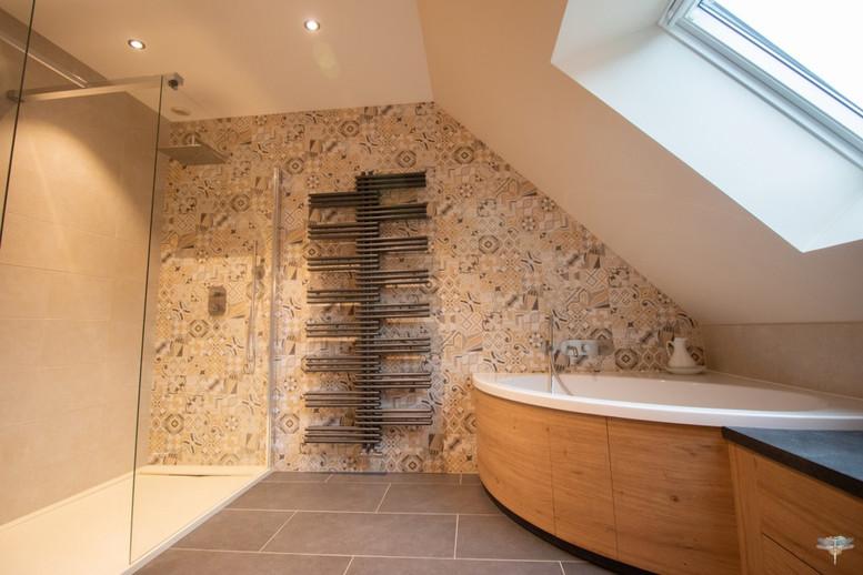 Agencement et décoration d'une salle de bains par Carnets Libellule. Coralie Vasseur est votre Décoratrice d'intérieur UFDI à Compiegne : vue d'ensemble d'une grande salle de bains sur-mesure avec douche receveur extra plat, baignoire d'angle et sèche serviette de