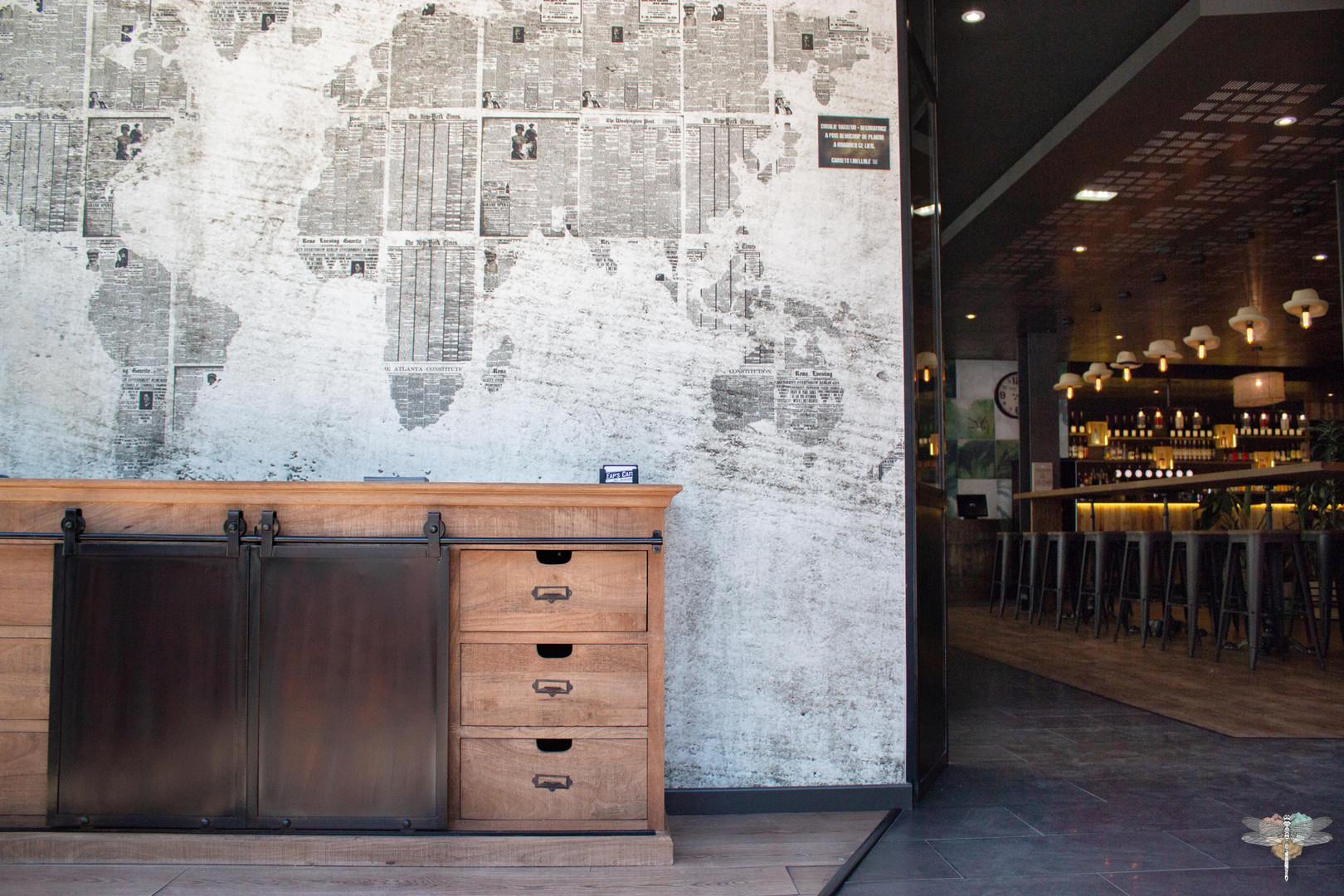 Agencement et décoration du restaurant industriel voyage EAP's CAFE par Carnets Libellule. Coralie Vasseur est votre Décoratrice d'intérieur UFDI à Compiegne : entrée avec meuble de métier et papier peint map monde