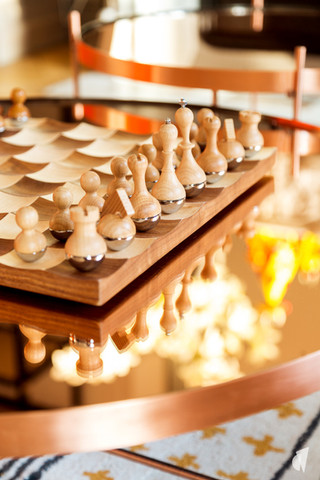 Aménagement et décoration d'un double salon et entrée dans un appartement Haussmannien revisité à l'ambiance design à Paris, par le Studio Coralie Vasseur. Coralie Vasseur est votre architecte d'intérieur et décoratrice UFDI à Annecy, Genève et en Haute Savoie : focus sur le jeu d'échec design en bois et la table basse cuivrée