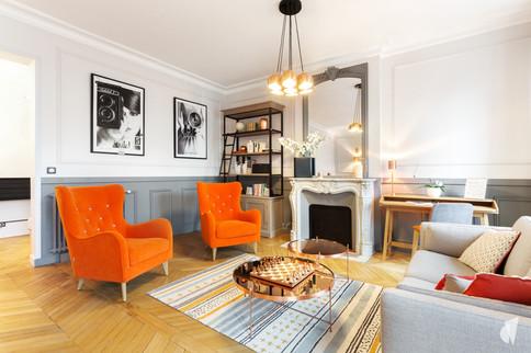 Aménagement et décoration d'un double salon et entrée dans un appartement Haussmannien revisité à l'ambiance design à Paris, par le Studio Coralie Vasseur. Coralie Vasseur est votre architecte d'intérieur et décoratrice UFDI à Annecy, Genève et en Haute Savoie : vue d'ensemble sur le salon de réception avec ses deux fauteuils oranges et le tapis graphique